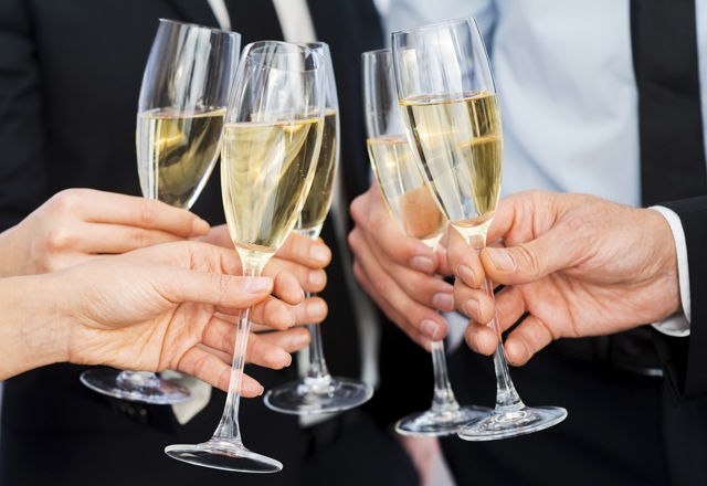 Cheers to success. Close-up of business people holding flutes wi