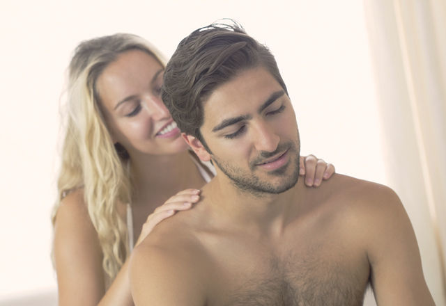 Smiling girlfriend kneading boyfriends shoulder in bedroom at home