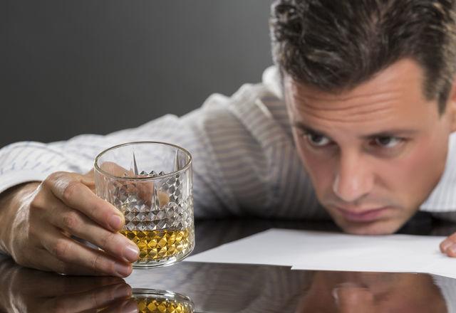 Sad businessman drinking alcohol