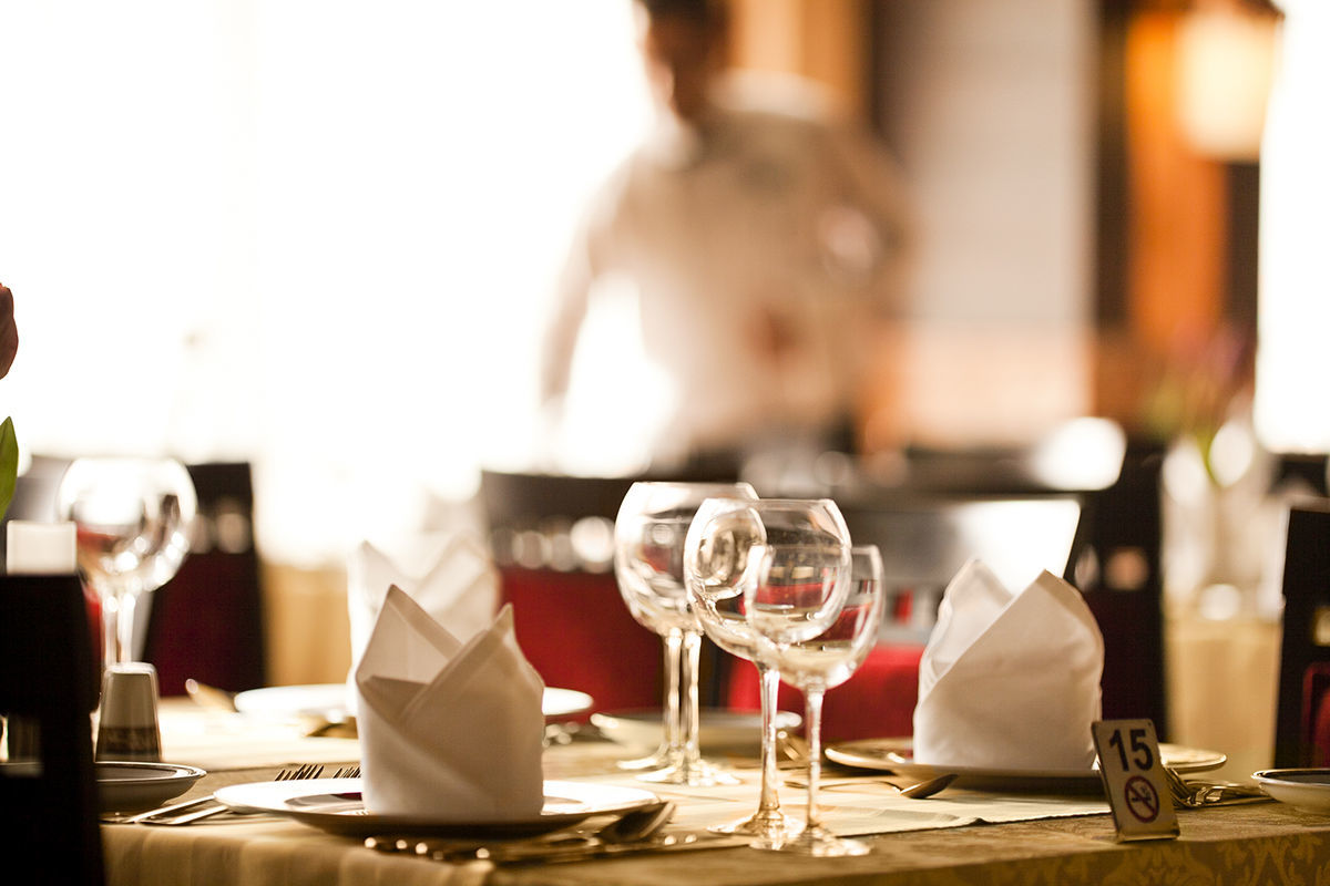 Waiter and Empty dining room of fancy restaurant