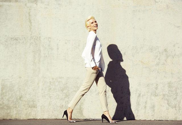 Smiling female fashion model walking