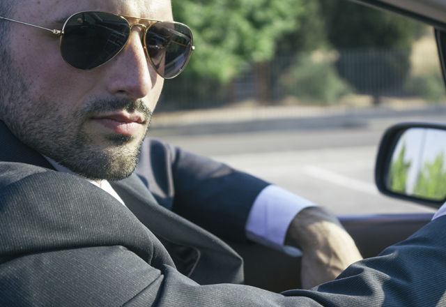 Businessman with sunglasses in a convertible car