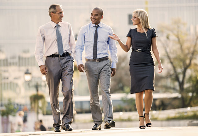 Three business people walking outdoors.