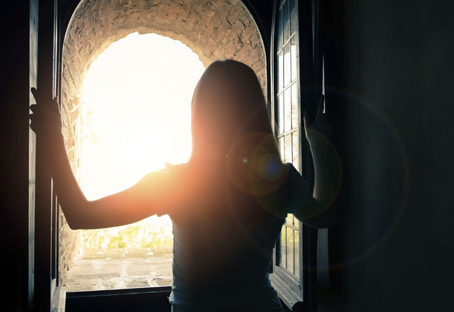 Woman opens windows and enjoys the landscape
