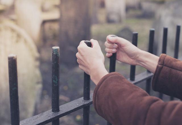 Hands holding fence at graveyard