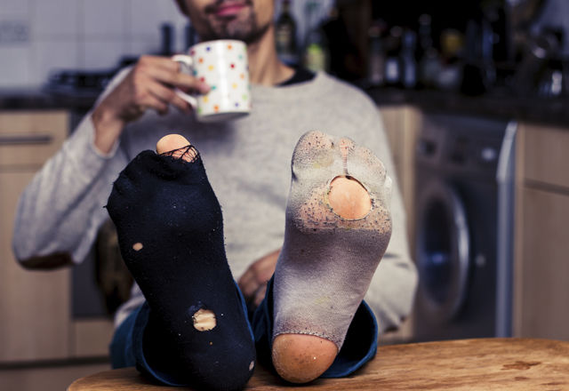 Man with worn out socks having coffee in kitchen