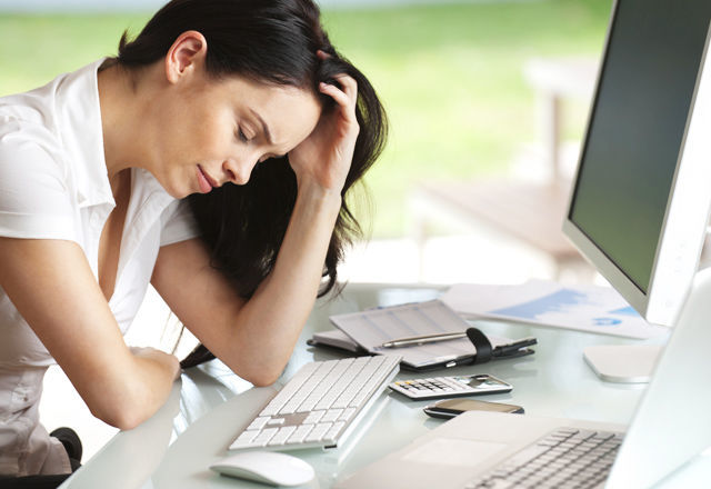 Woman looking stressed at her desk