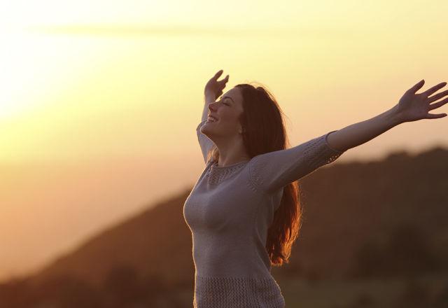 Woman at sunset breathing fresh air raising arms