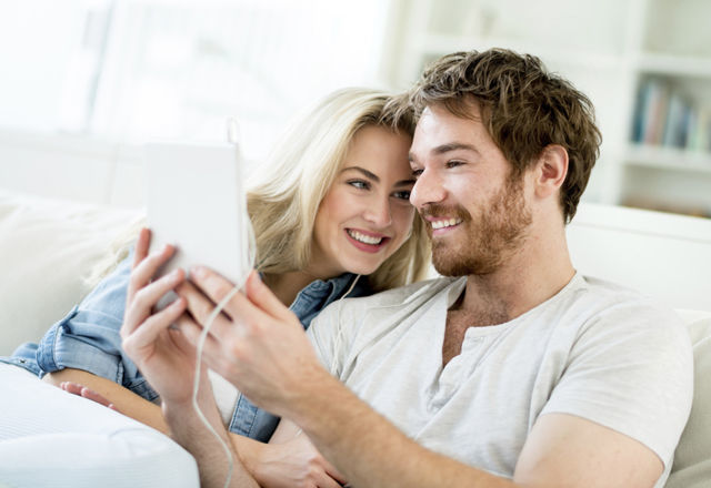 Couple video chatting on a tablet computer at home