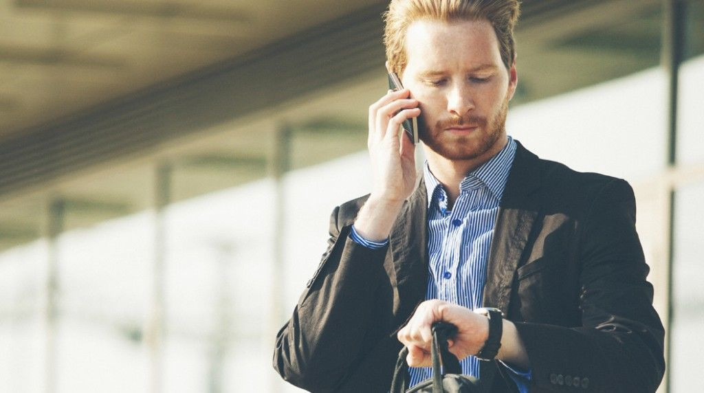 Young businessman checking time and talking on the cell phone