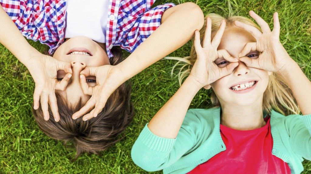 Summer fun. Top view of two cute little children making faces an
