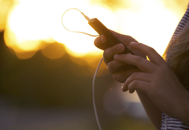 Young woman using a mobile phone with headphones outdoors.