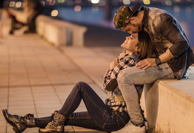 Romantic man kissing his girlfriend on a forehead at night.
