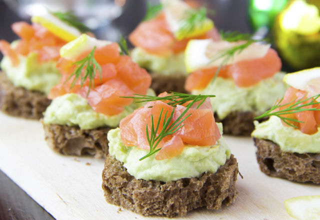 Appetizer canapes of bread with avocado, red fish salmon, lemon,