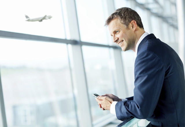 Smiling Businessman Looking Out Airport Window.