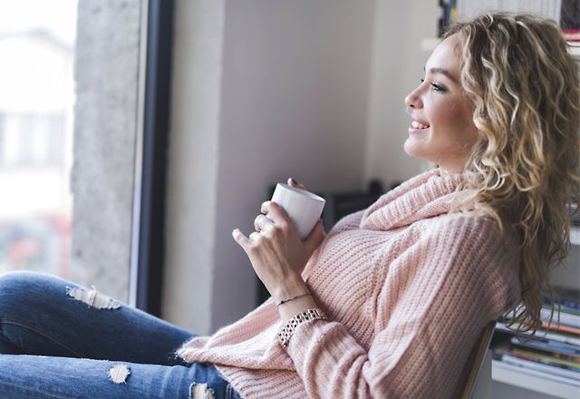 Young smiling woman enjoying in her coffee time.