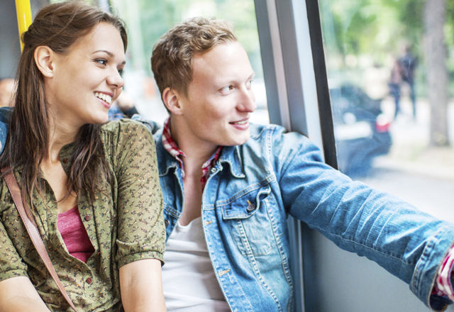 Young couple in a bus looking through window.