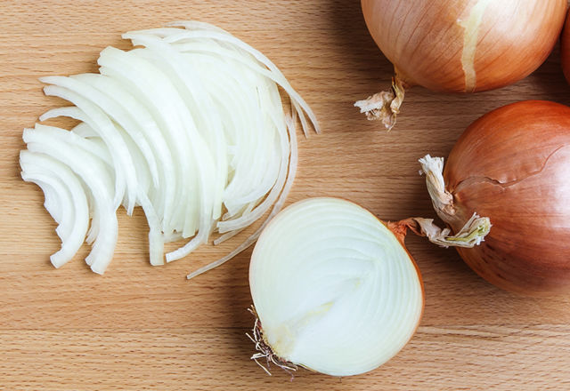 Whole and sliced onions on wooden cutting  board