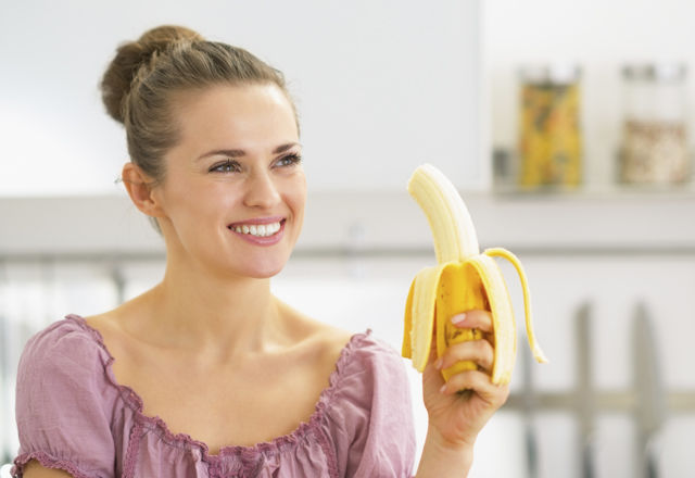 Happy young woman eating banana in kitchen