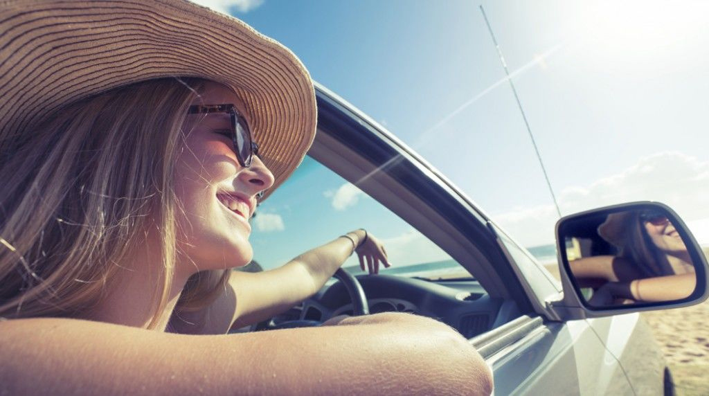 Woman looking out of a car window at the beach