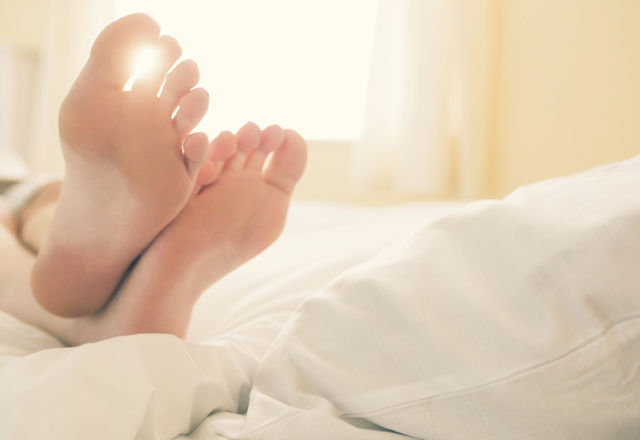 Close up of the feet of a girl lying on her bed in a sunny bedroom at home