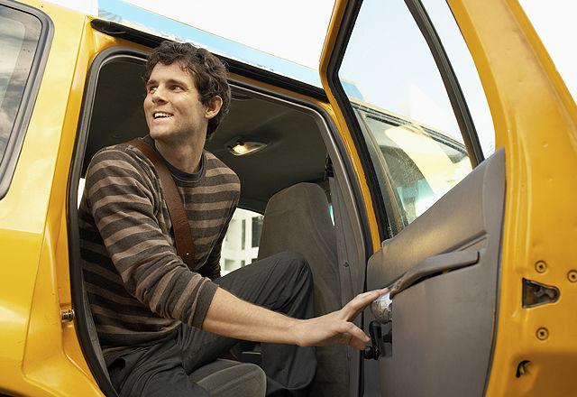 Young Man Disembarking Taxi
