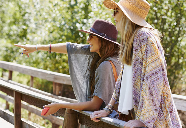 Two young woman standing on bridge pointing at view