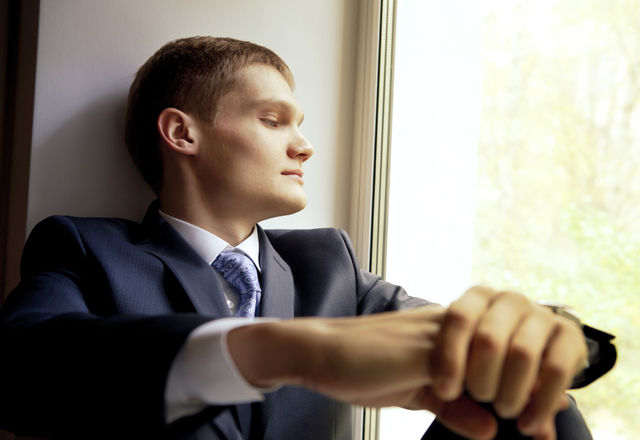 Young man sitting on windowsill waiting bride