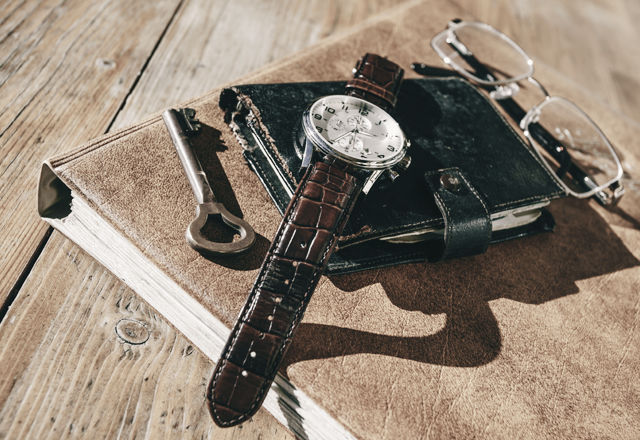 Man wristwatch, calendar, key and glasses on a old table.