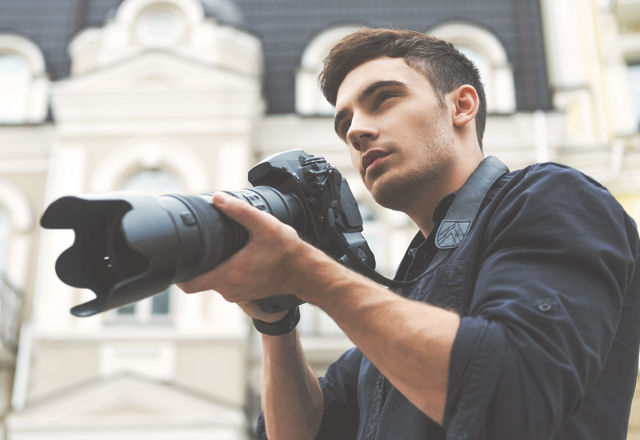 Ready to shoot. Low angle view of young man holding camera while