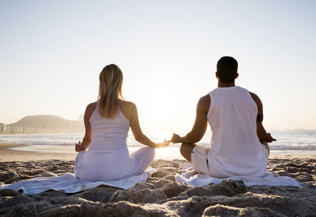 Couple meditating on the beach.
