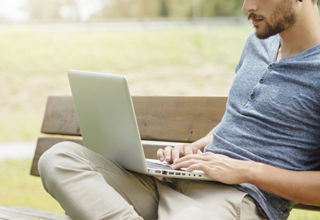 Handsome man using a laptop in the park