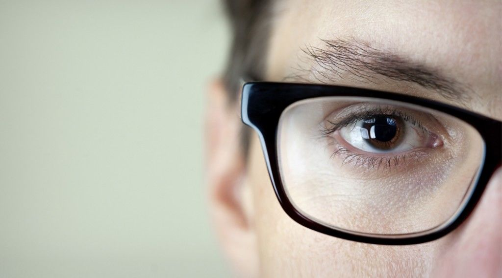 Close-up shot of a mans brown eye and glasses