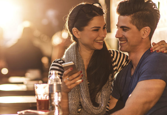 Smiling couple looking at each other and using cell phone.
