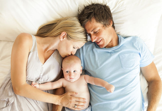 Parents With Baby In Bed