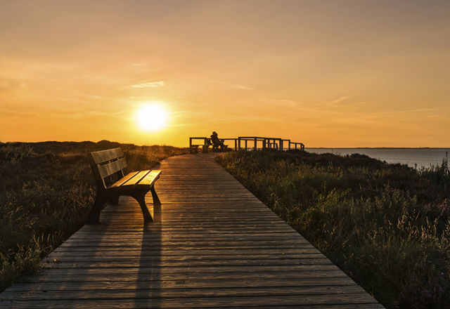 lonely bench on seacoast footpath and beauty sunset