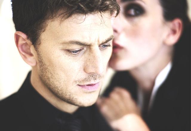 Secret, young woman talking into a man's ear _ Horizontal