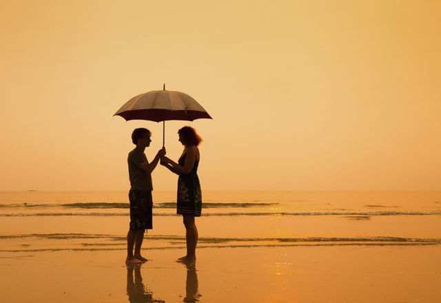 family on the beach, silhouettes of couple with umbrella