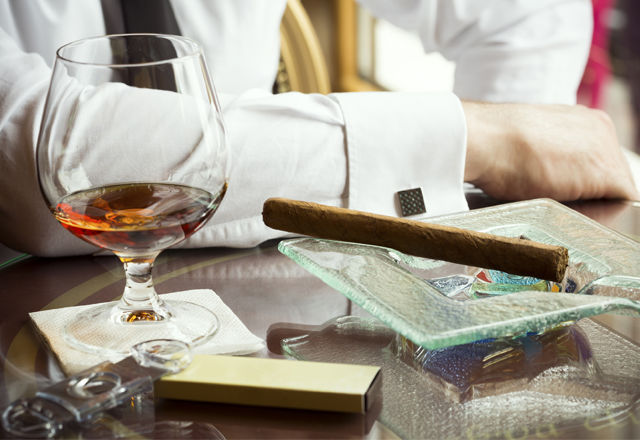 Man sitting in a bar with cognac and cigar