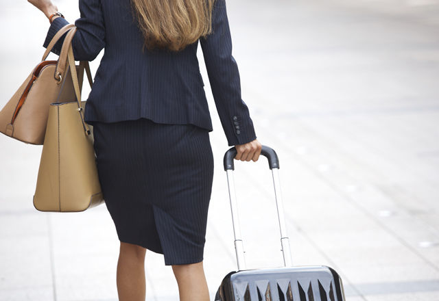 Businesswoman traveling with luggage and handbags