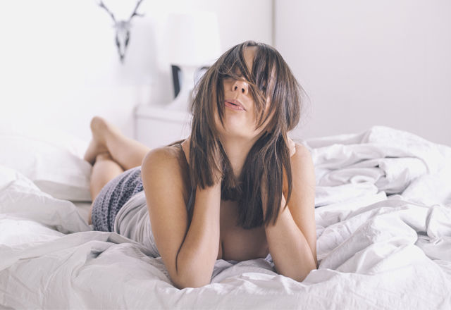 Young woman whistling as she lies awake in bed.