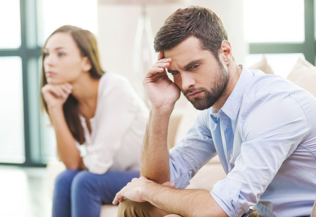 Relationship breakdown. Depressed young man holding hand on head
