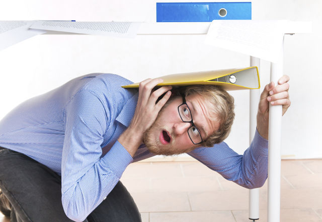 Frightened employee hiding under the desk