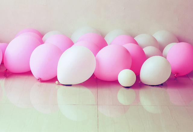 pink and white balloon on floor with white wall background