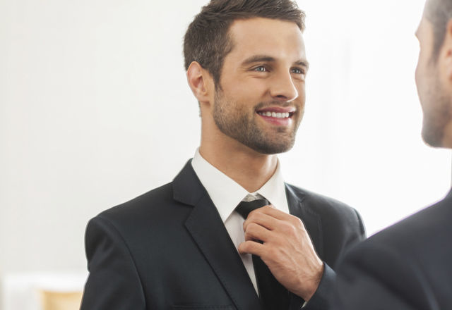 Used to look perfect. Handsome young man in formalwear adjusting