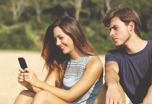 Jealous boyfriend watching his girlfriend texting on the phone