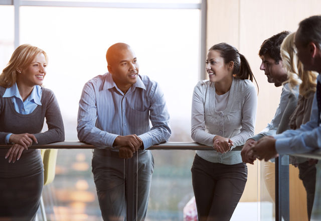 Group of laughing  businesspeople talking in a lobby.
