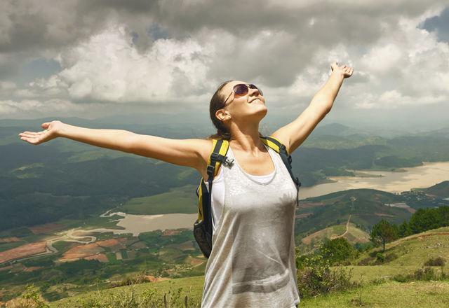 Portrait of happy traveler girl with raised up hands enjoying va
