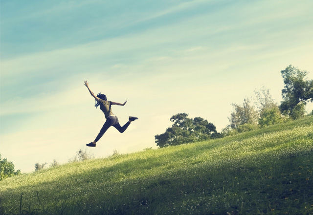 woman running and jumping funny relax on green grass and flower