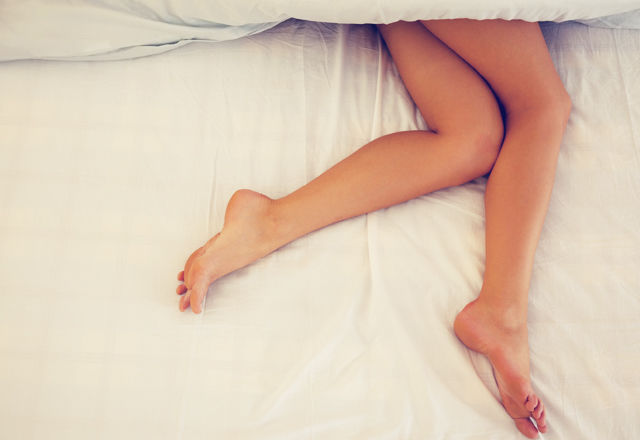 Legs of a young woman lying in her bed sleeping at home